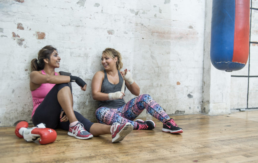 women sitting down smiling in a boxing gym in Cardiff