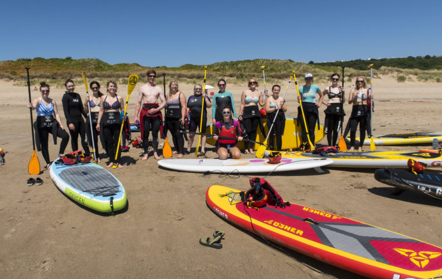 Giorgia Rescigno, Jojo Jayne with a group of women on a sunny day on a beach in Gower, Wales for a Standup Paddle boarding and yoga day.