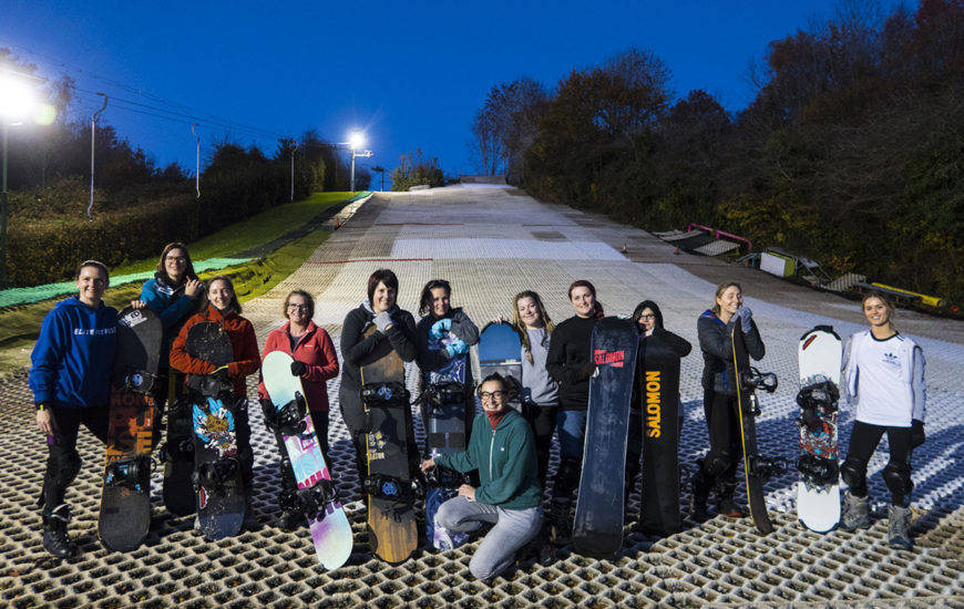 A group of women standing on Cardiff Ski and Snowboard dry slope with their snowboards smiling. Women's beginner snowboarding class