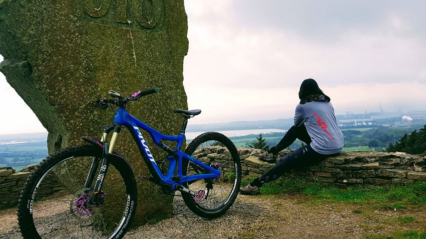 Women's Mountain Biking adventure and coaching day. image of a woman, Sarah Wakefield with a mountain bike staring into the beautiful landscape in Wales