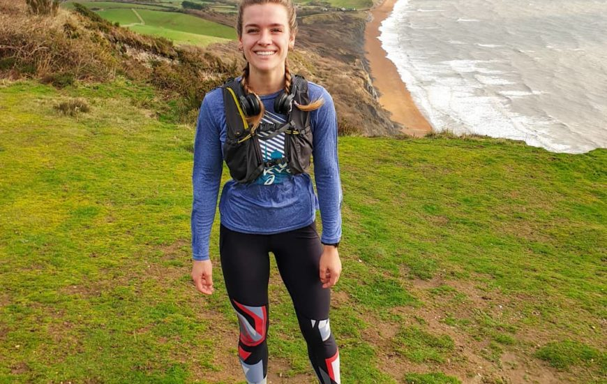 Flora Beverley with running gear on, at the top of a hill in Dorset