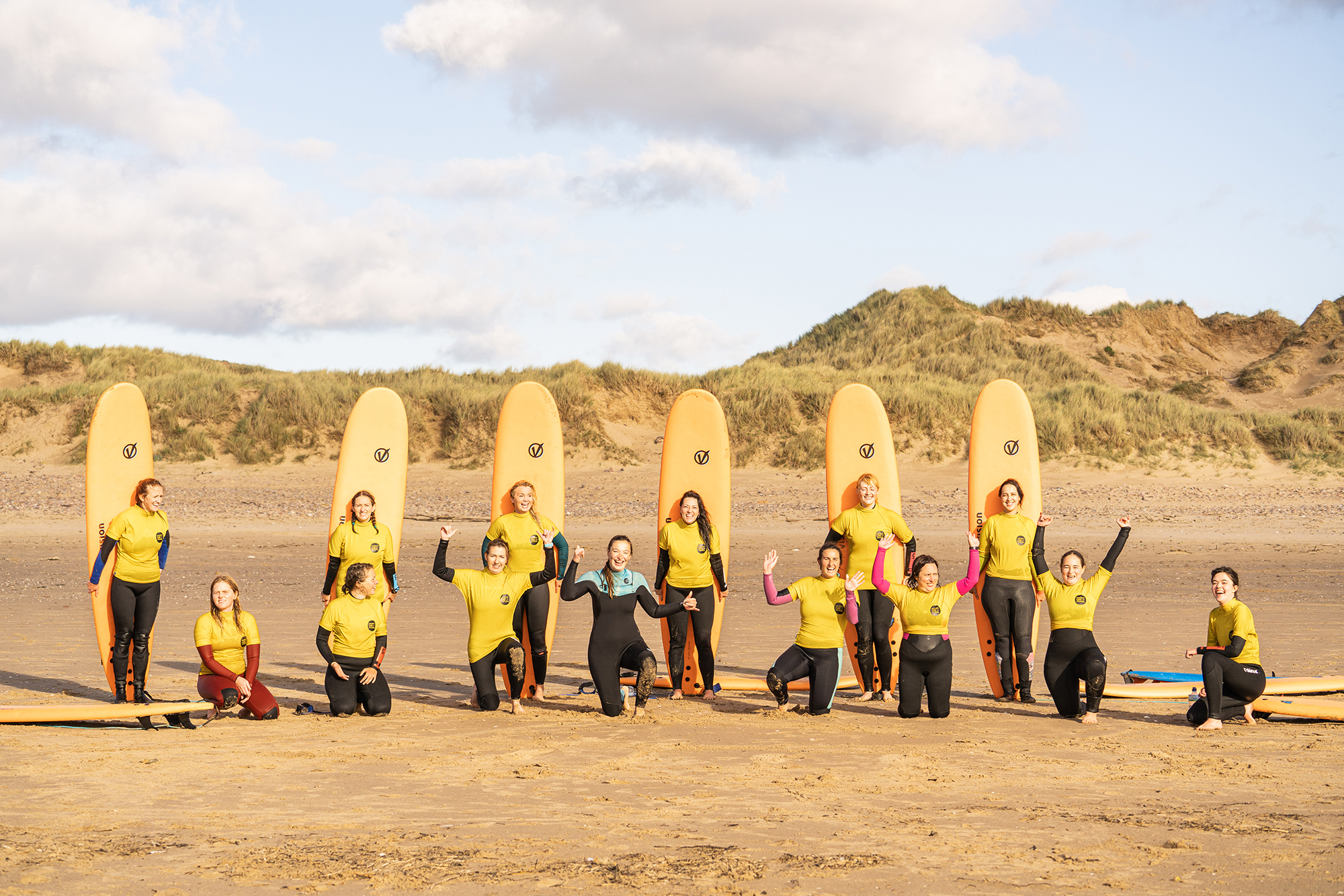 group of women on the beach in gower with surf boards
